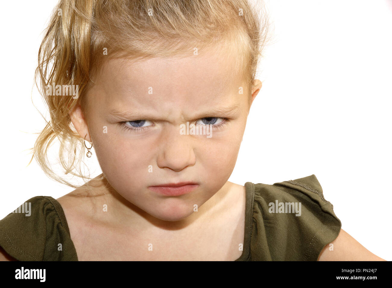 Six year old girl scowling at camera - Stock Image