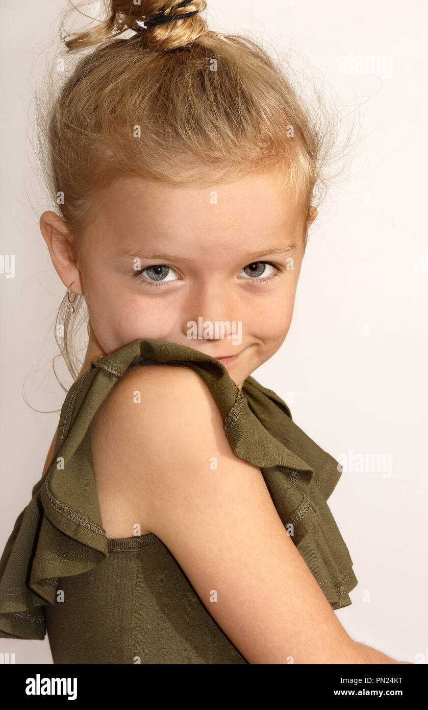Six year old girl shyly looking over her shoulder - Stock Image