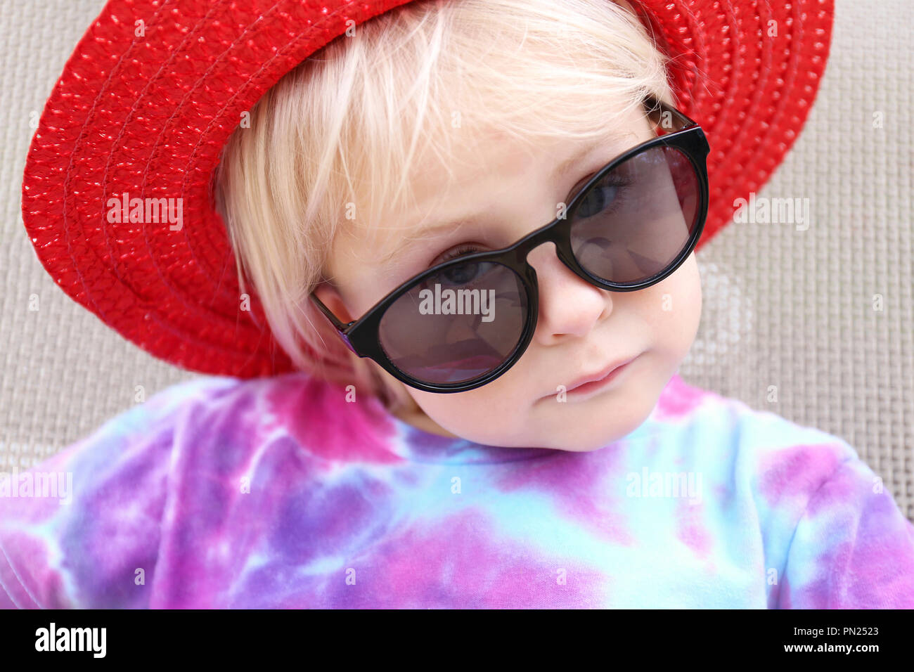 029e20af0a9a A cute little 2 year old toddler girl is sunbathing outside, wearing a red  summer