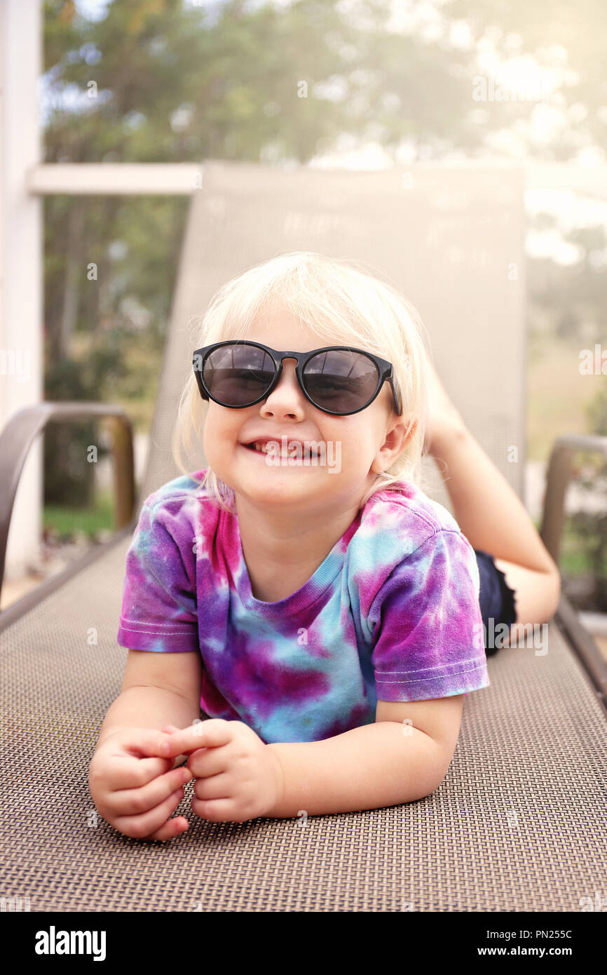 A Cute 2 Year Old Toddler Child Is Smiling As She Poses For The Camera On A Beach Chair Under The Creen By The Pool On A Summer Day Stock Photo Alamy