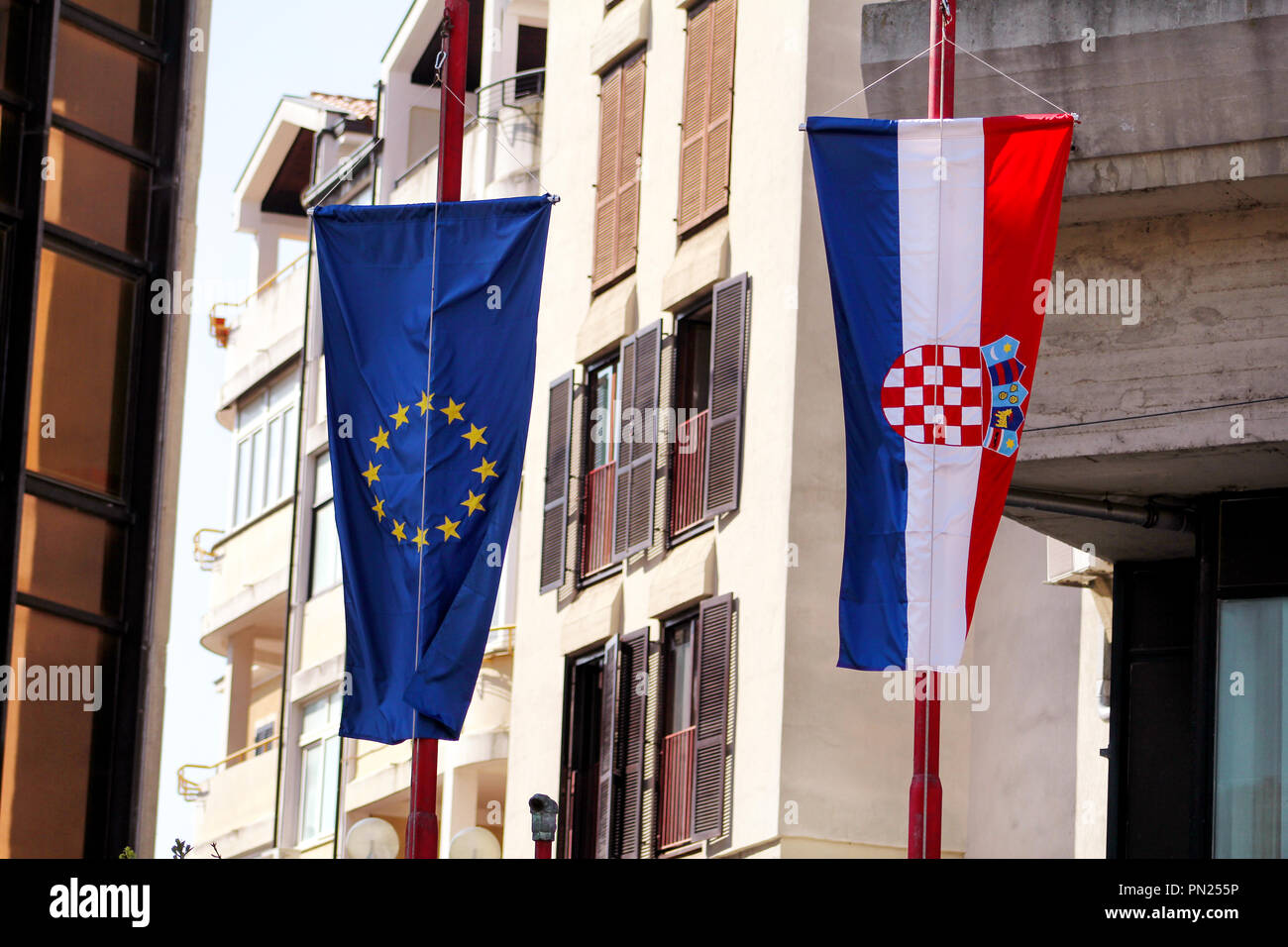 Flags of the European Union and Croatia on the street. In the background a detail of the building. Croatian and EU flag. - Stock Image