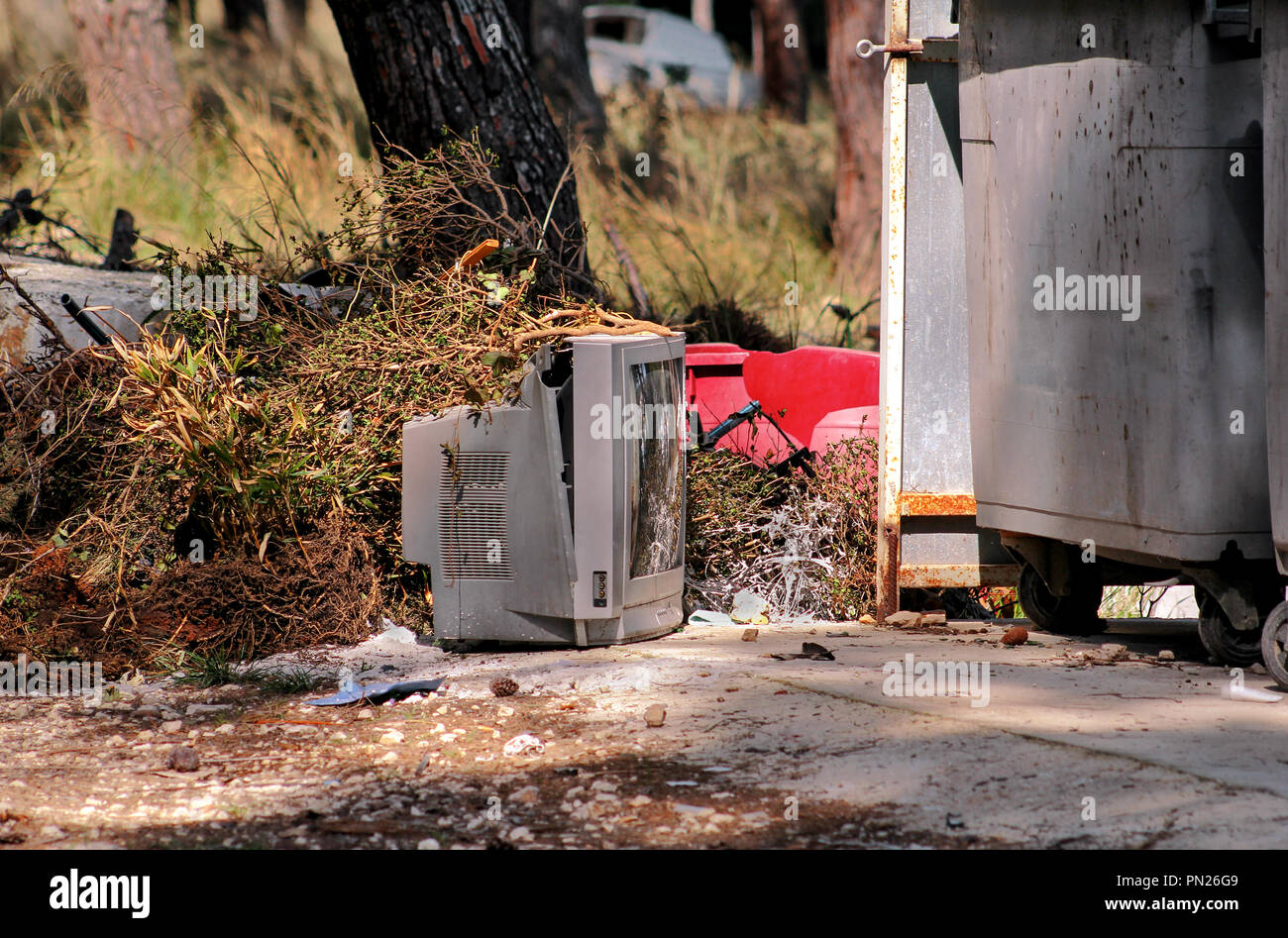Discard old TV sets on a street, television near the container thrown, the natural environment. A TV thrown out with the garbage. Throwing out garbage - Stock Image