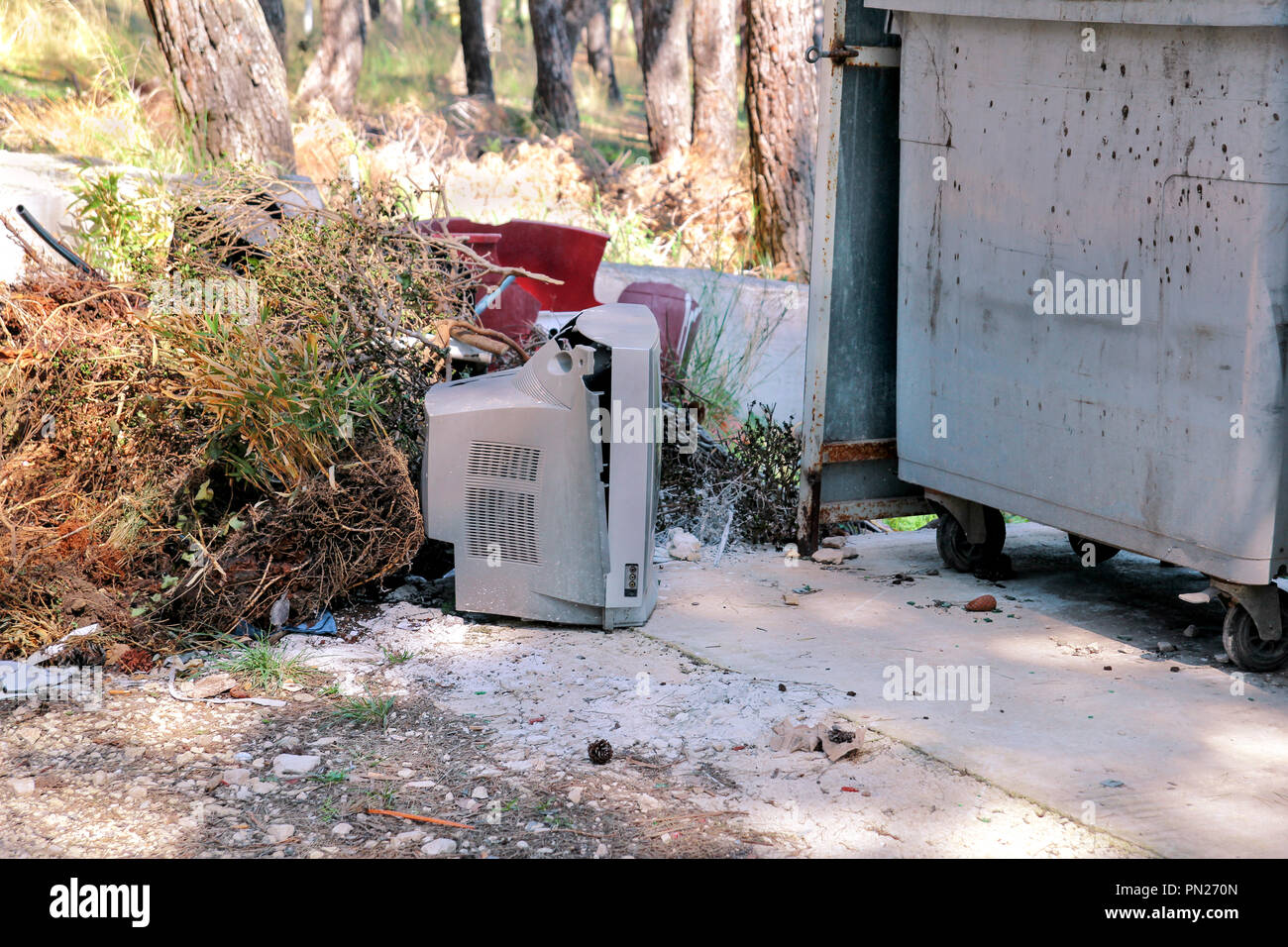 Discard old TV sets on a street, television near the garbage container thrown, natural environment. A TV thrown out with the garbage. Throwing out. - Stock Image