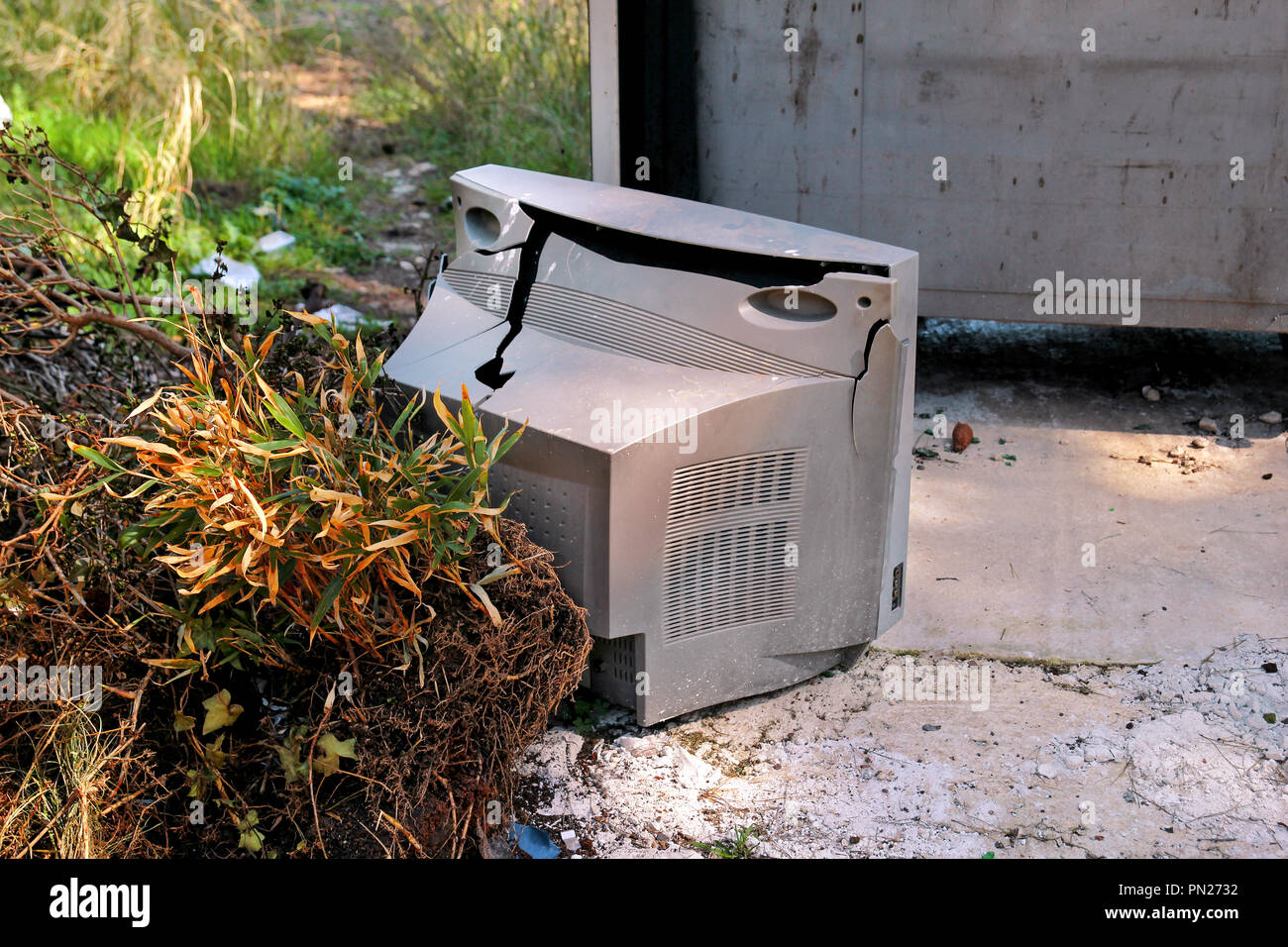 Discard old TV sets on a street, television near the garbage container thrown, natural environment. A TV thrown out with the garbage. Throwing out - Stock Image