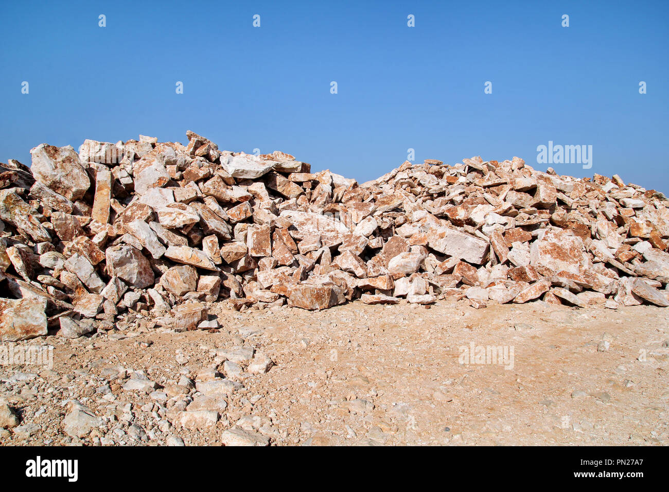 Brown Granite. Big pile of rocks for construction and boulders piled in a heap under a blue sky in summer time. A large pile of limestone in quarry. - Stock Image