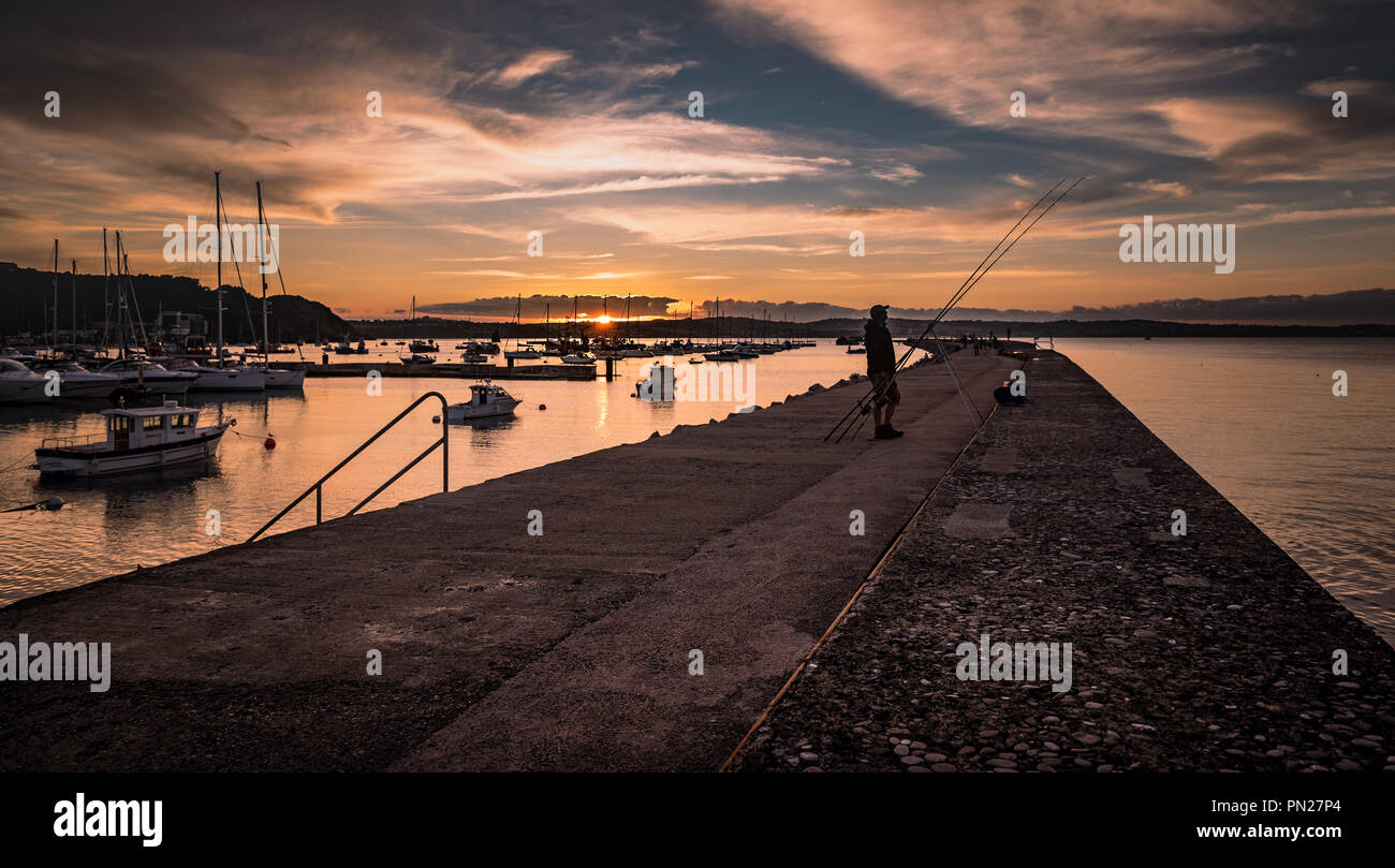 Fisherman at sunset on Brixham breakwater - Stock Image