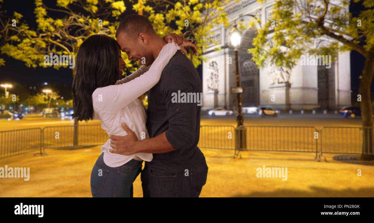 Black male visiting girlfriend in Paris meets her near Arc de Triomphe - Stock Image