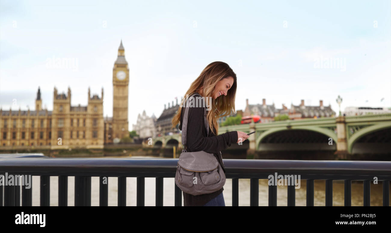 Caucasian woman lost in London uses smartphone for directions - Stock Image
