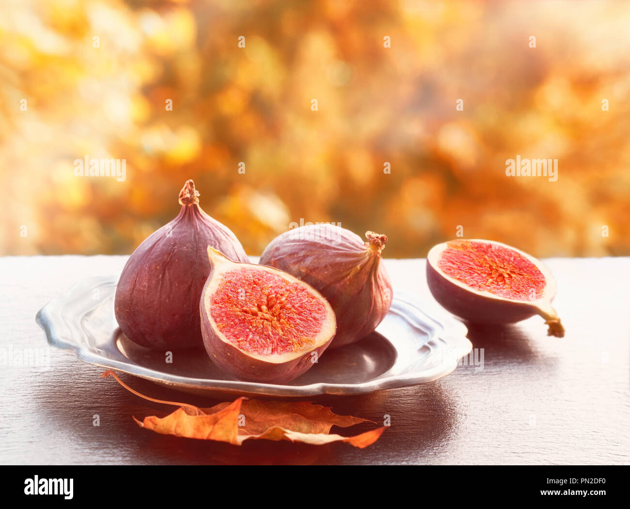 Closeup on fresh figs on dark shiny stone plate outdoors, toned image, text space - Stock Image