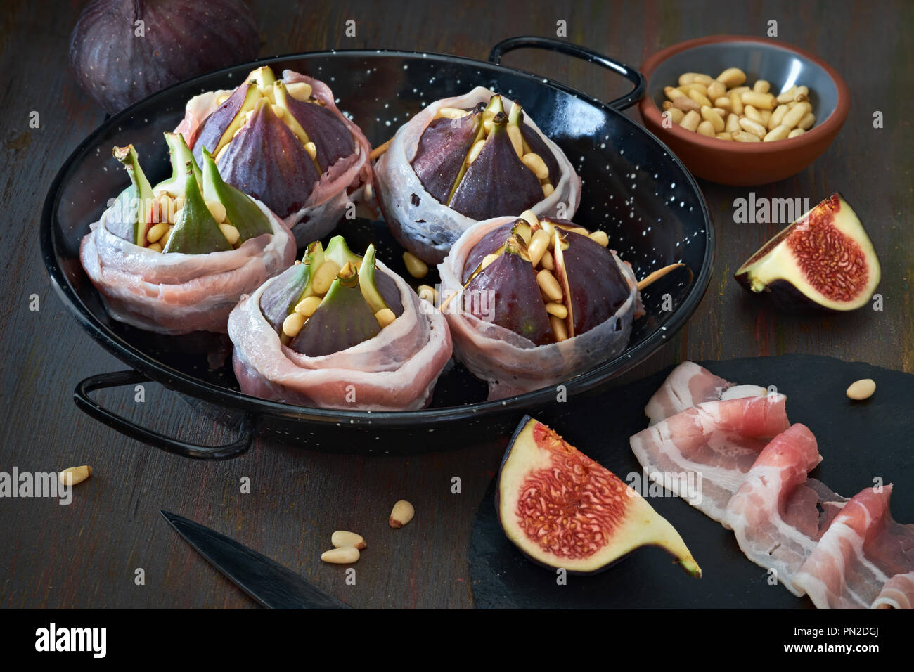 Preparation and ingredients for baking figs stuffes with pine nuts and wrapped in bacon slices - Stock Image