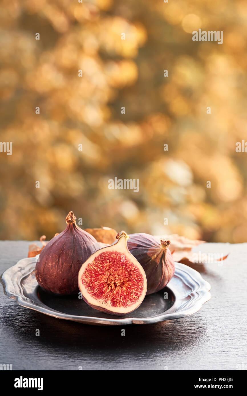 Closeup on fresh figs on dark shiny stone plate outdoors, toned image - Stock Image