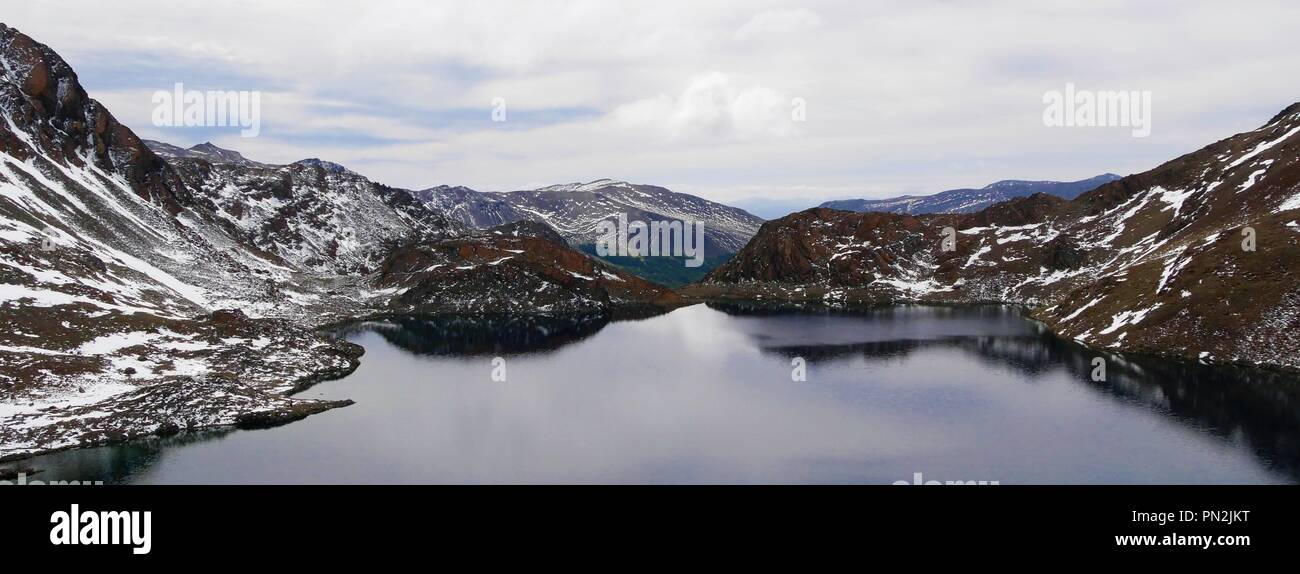 Panorama of mountains reflecting on a lake at Dientes de Navarino Trek close to Puerto Williams in Tierra del Fuego / Patagonia in Chile - Stock Image
