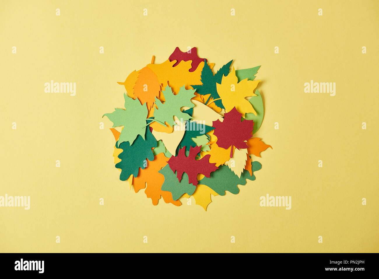 flat lay with colorful papercrafted foliage arranged in cirlce on yellow background - Stock Image