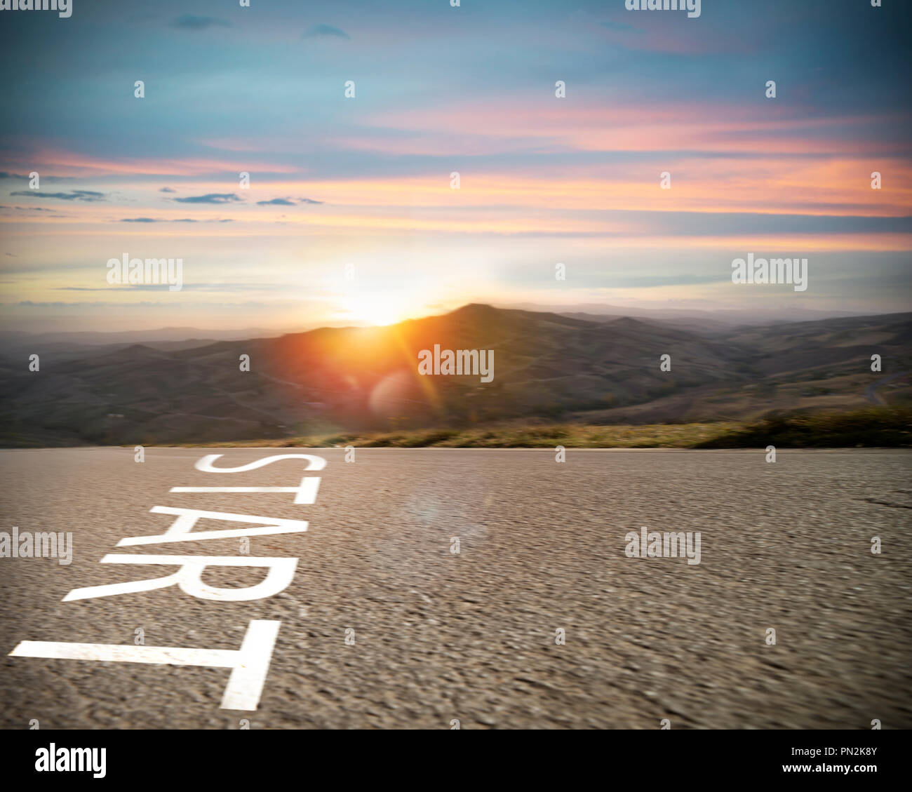 Start written to the ground on a road at sunset. Concept of new beginning and starting new opportunities - Stock Image