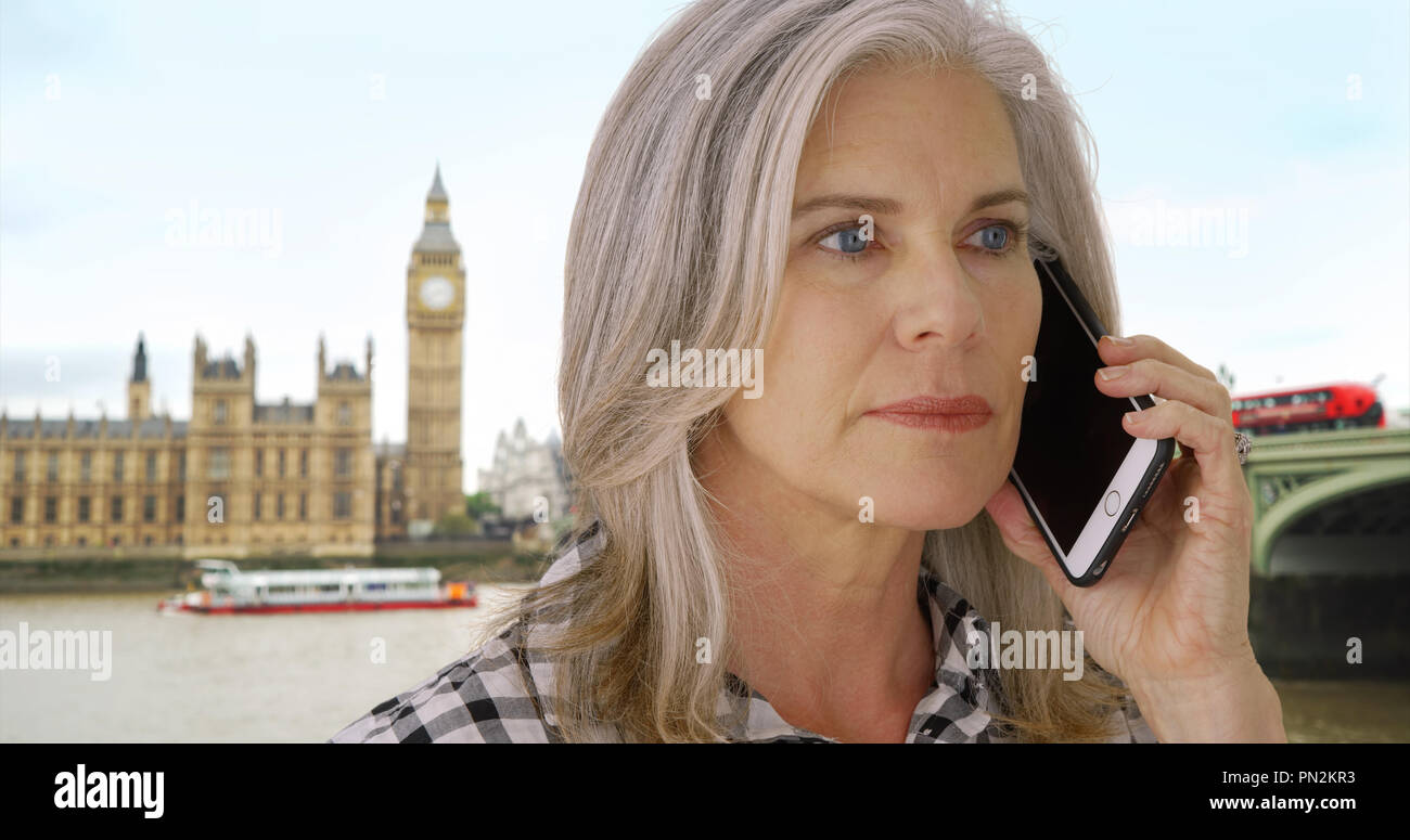 Concerned old white woman in London receives distressing call on her smartphone - Stock Image
