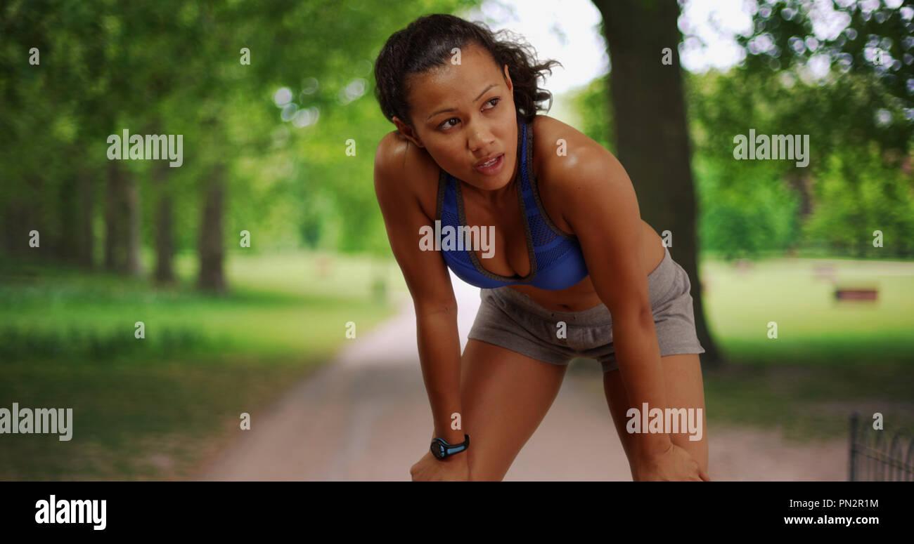 Filipino woman athlete taking jogging break at the park in daytime - Stock Photo
