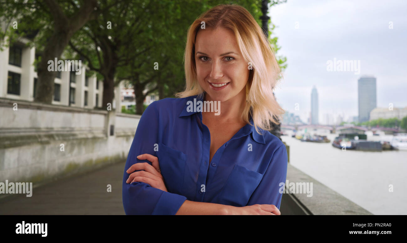 Happy young Caucasian female in blue buttoned shirt posing by River Thames - Stock Image