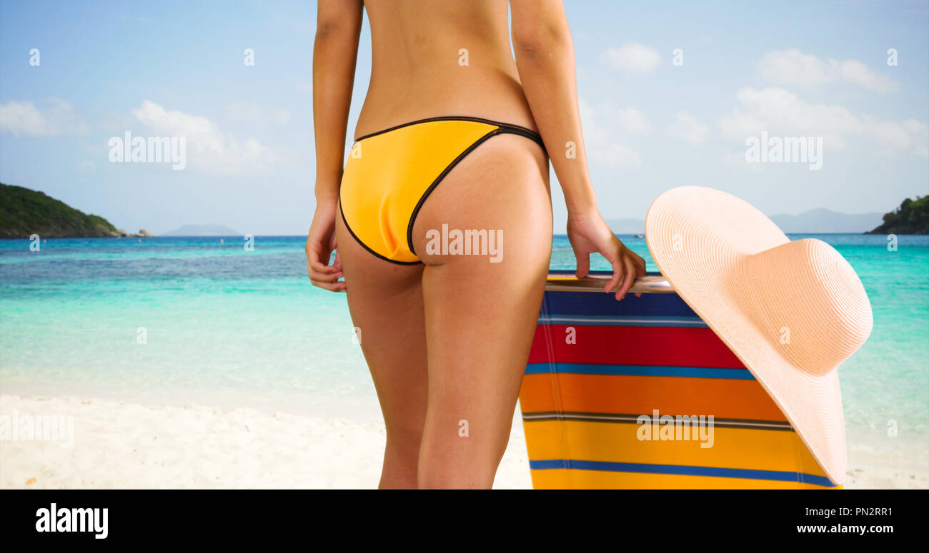 Medium shot of a young white girl standing next to her lounge chair in her yellow bikini - Stock Image