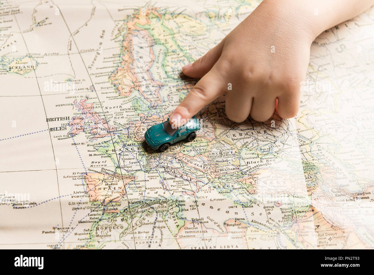 Travel concept. Hand of a child and toy car on map of Europe. - Stock Image