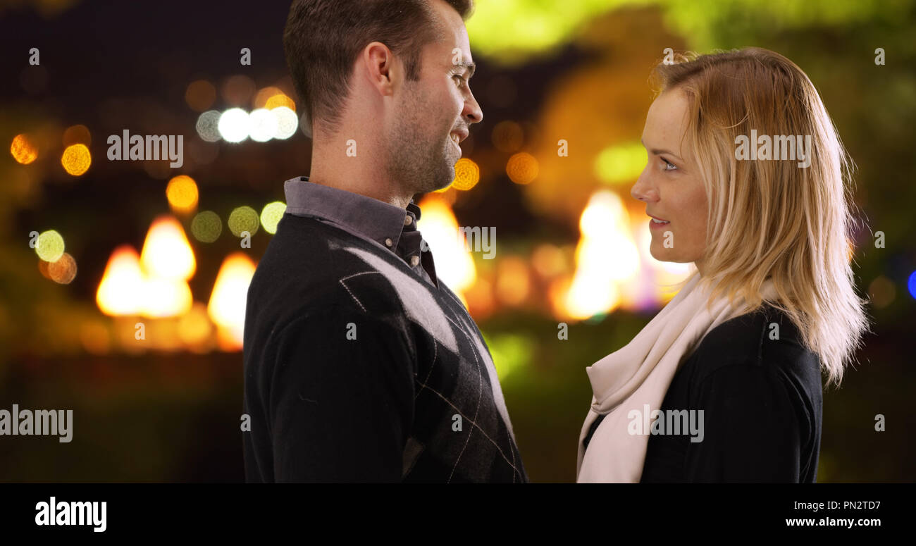 Loving young couple looking into each others eyes outdoors - Stock Image