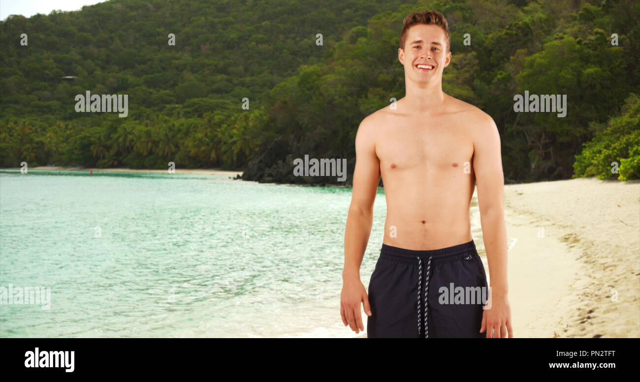 Portrait of attractive guy standing shirtless in swim shorts on Caribbean beach. - Stock Image