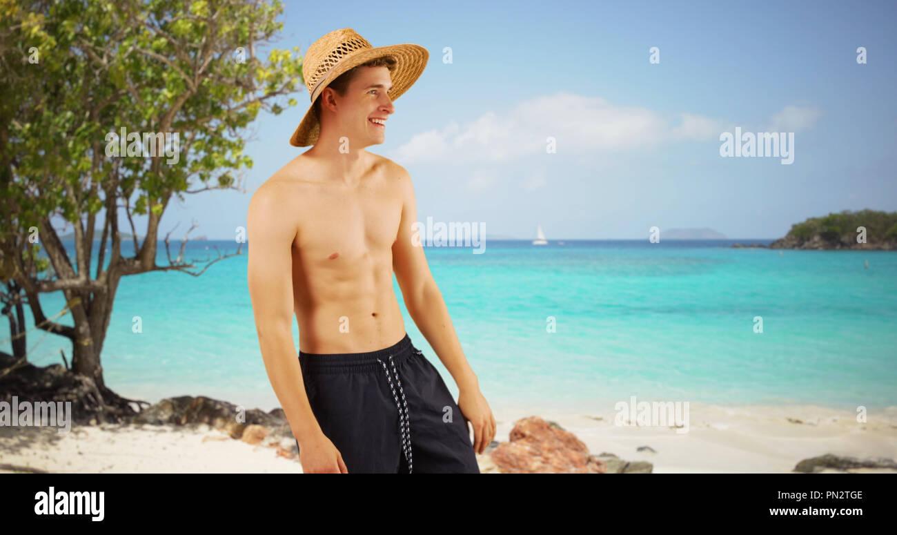 Portrait of man wearing swim shorts on St. John island beach. - Stock Image