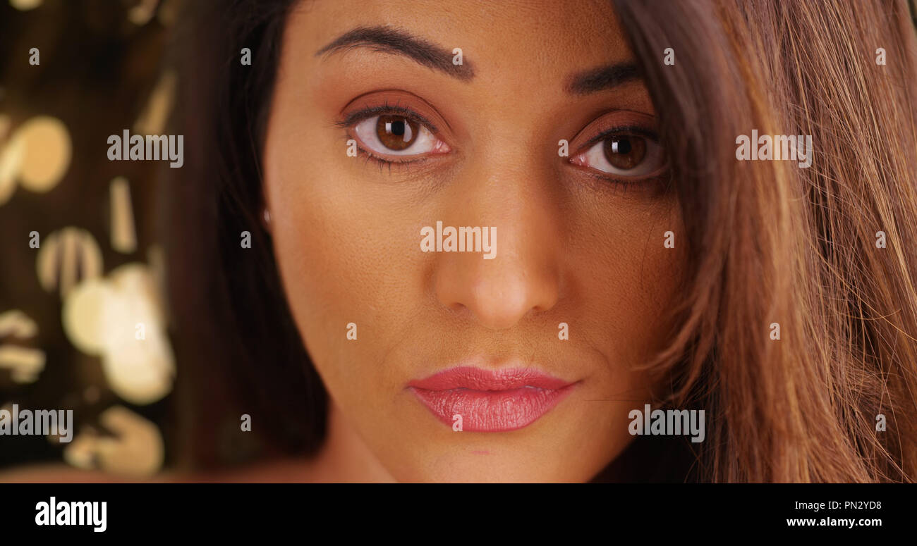 Closeup of sultry Latina female looking at camera confidently outside in evening - Stock Image