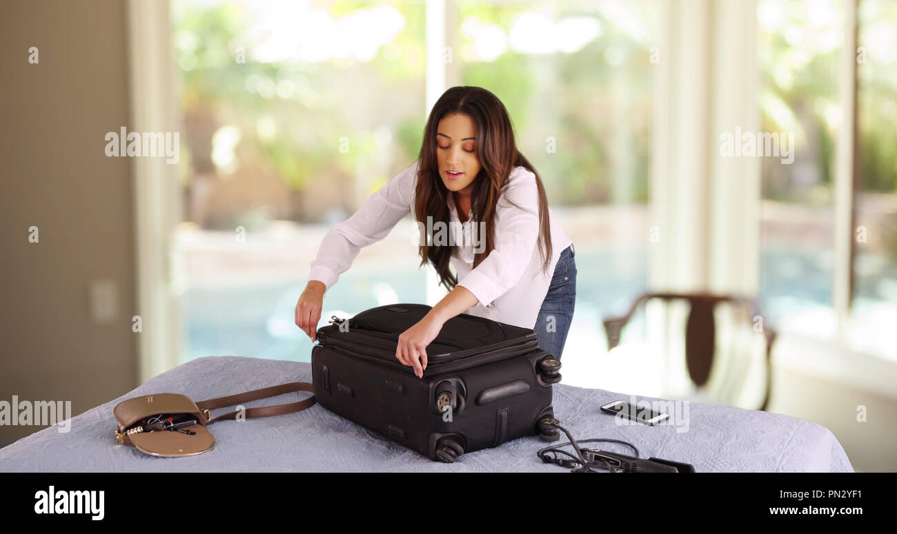 Cheerful Cuban female zipping up suitcase leaving for fun summer vacation - Stock Image