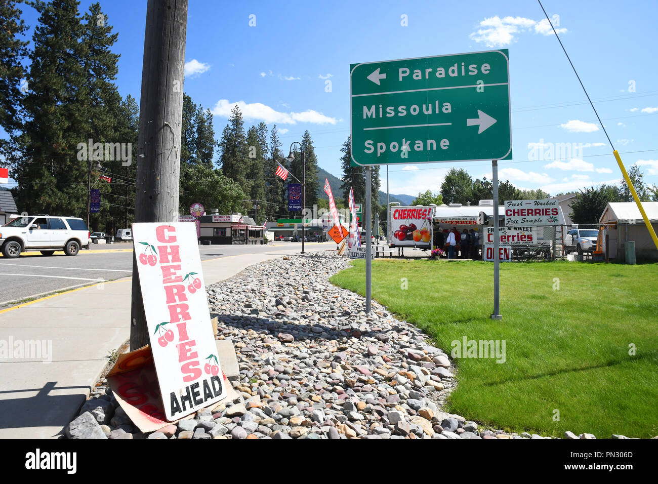 ST. REGIS, MONTANA, USA: September 1, 2018: Sign points to Paradise, Missoula and Spokane with a cherry stand in behind it Stock Photo