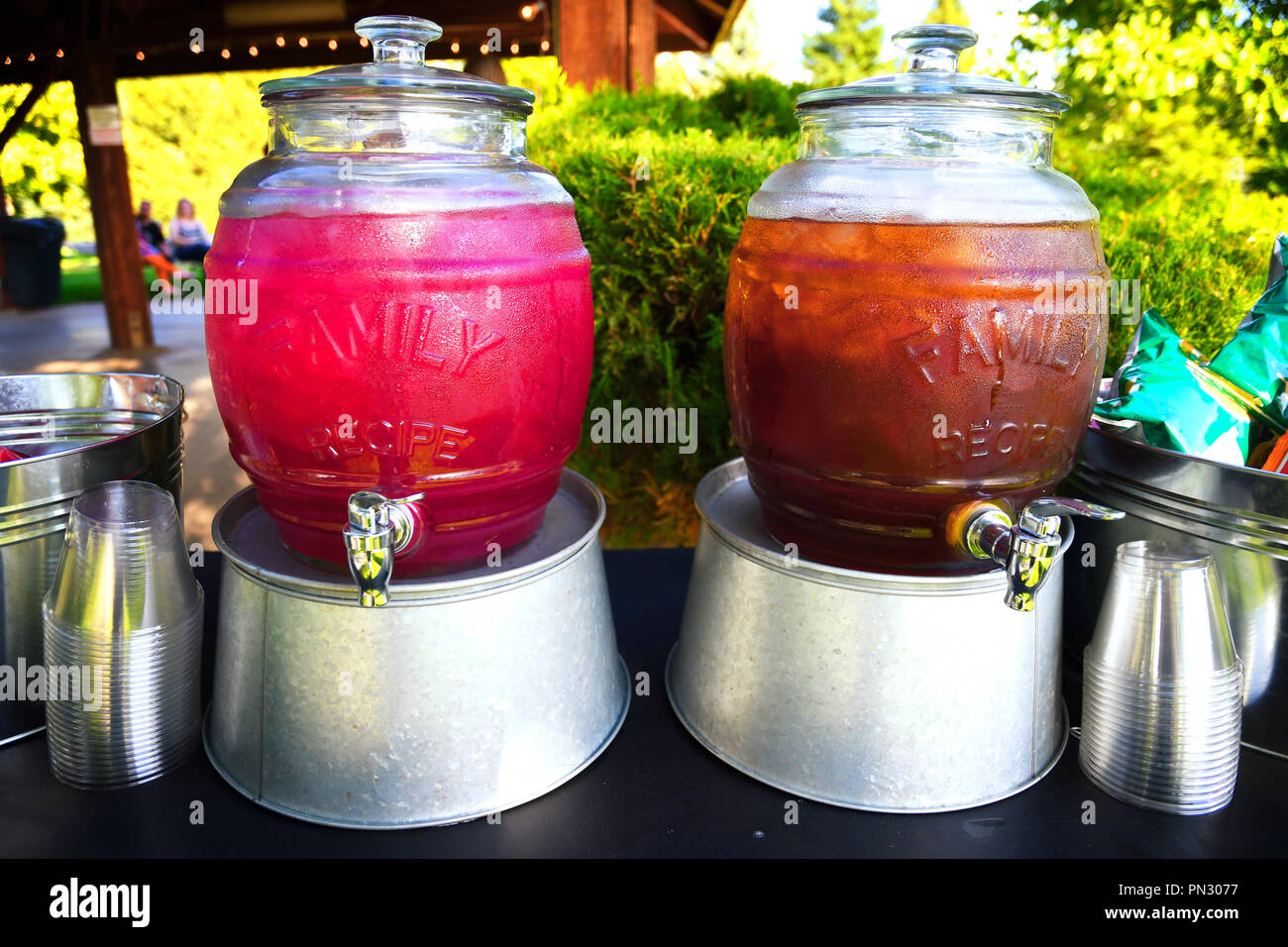Jugs of cold huckleberry lemonade and iced tea on galvanized aluminum tubs displayed at an outdoor event - Stock Image