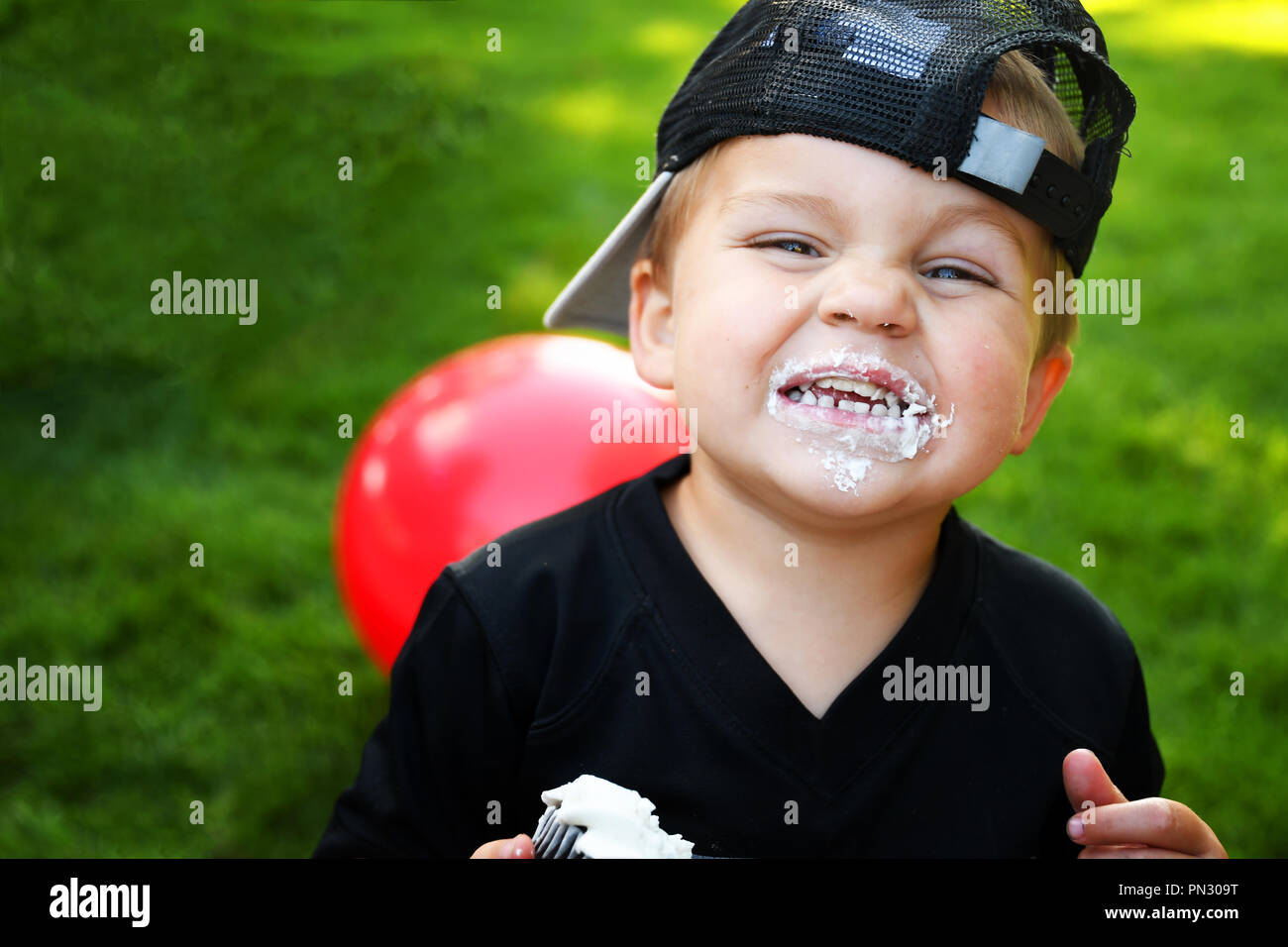 A smiling little boy with white frosting on his face Stock Photo