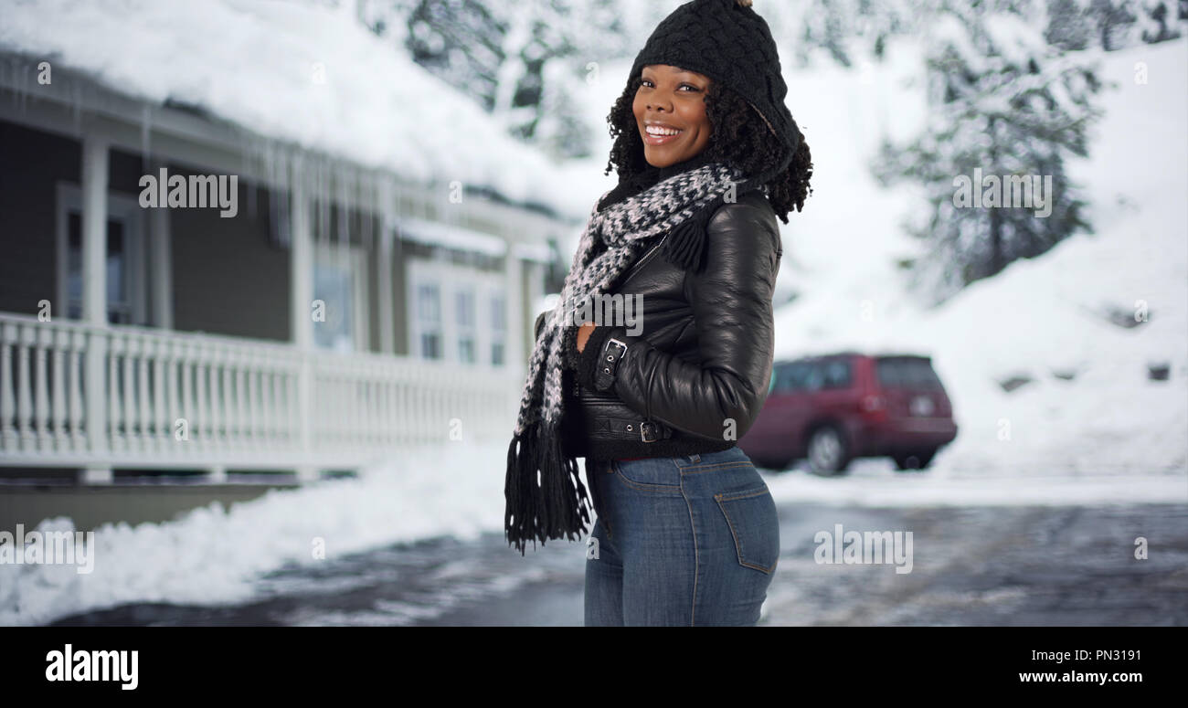 453bdba1bc2 Cute black woman in cozy hat and scarf standing outside home in snow smiling