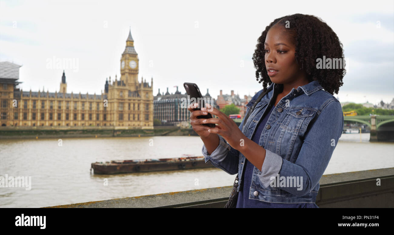 Pretty black woman traveling in London looking at map app on cell phone - Stock Image