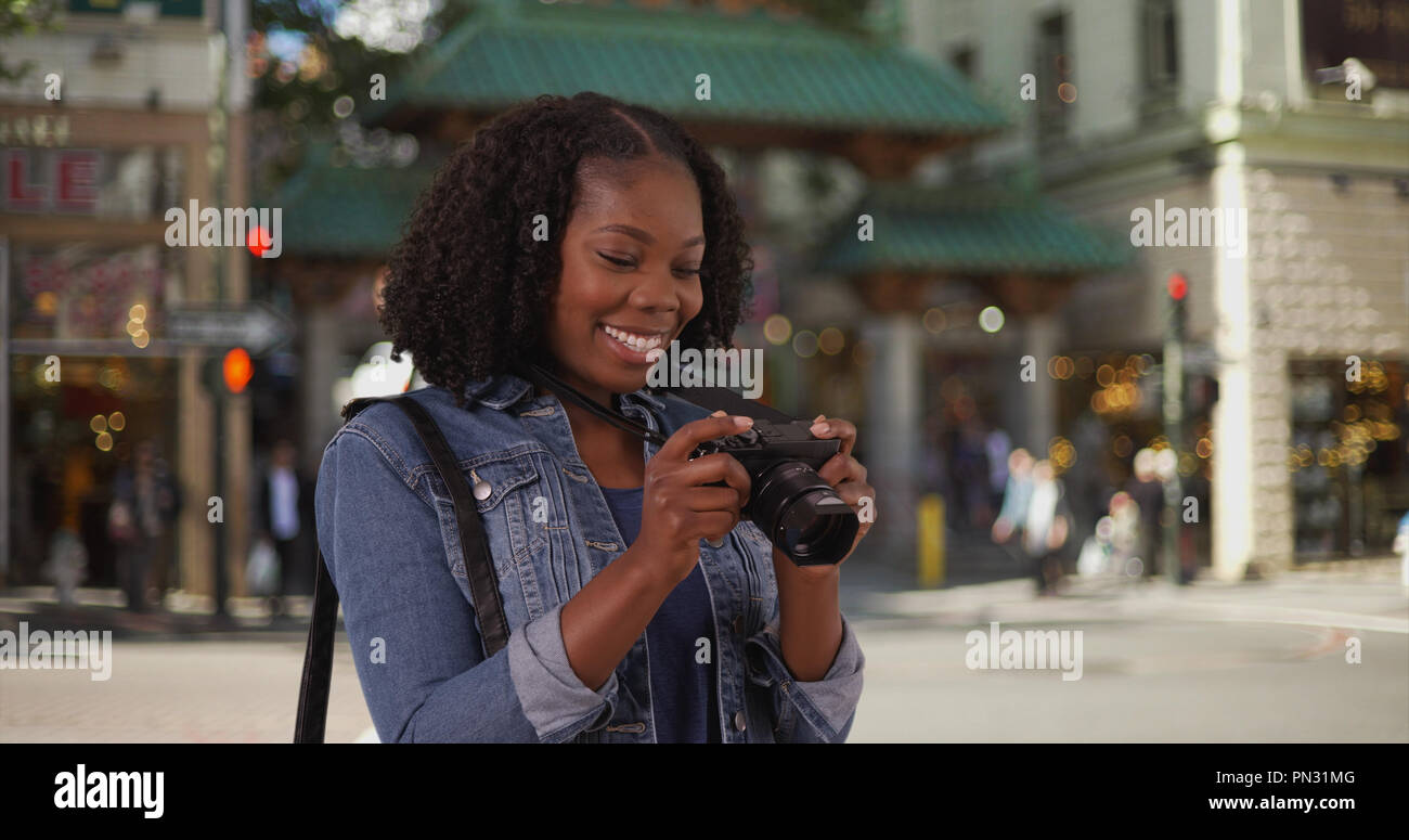 Attractive black woman takes picture near Chinatown entrance in San Francisco Stock Photo