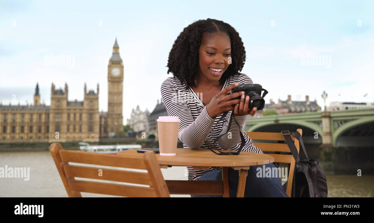 Cute black female sits at table along River Thames browsing photos on camera - Stock Image