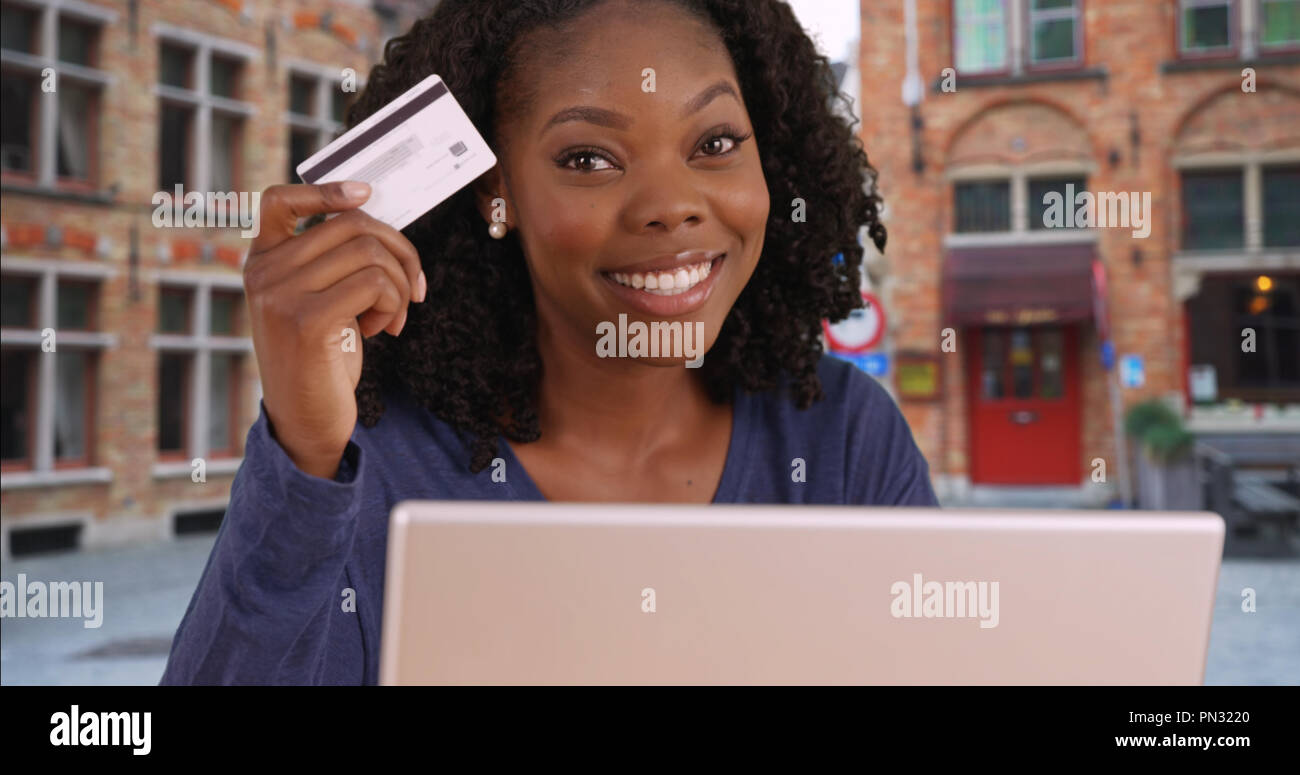 Smart financially independent black woman holding up credit card and smiling - Stock Image