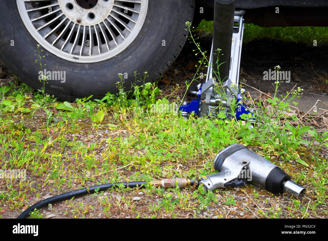Car jack and impact torque wrench near a car tire Stock Photo