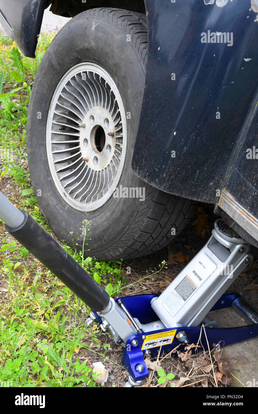 Car jack underneath a car after fixing a flat tire Stock Photo