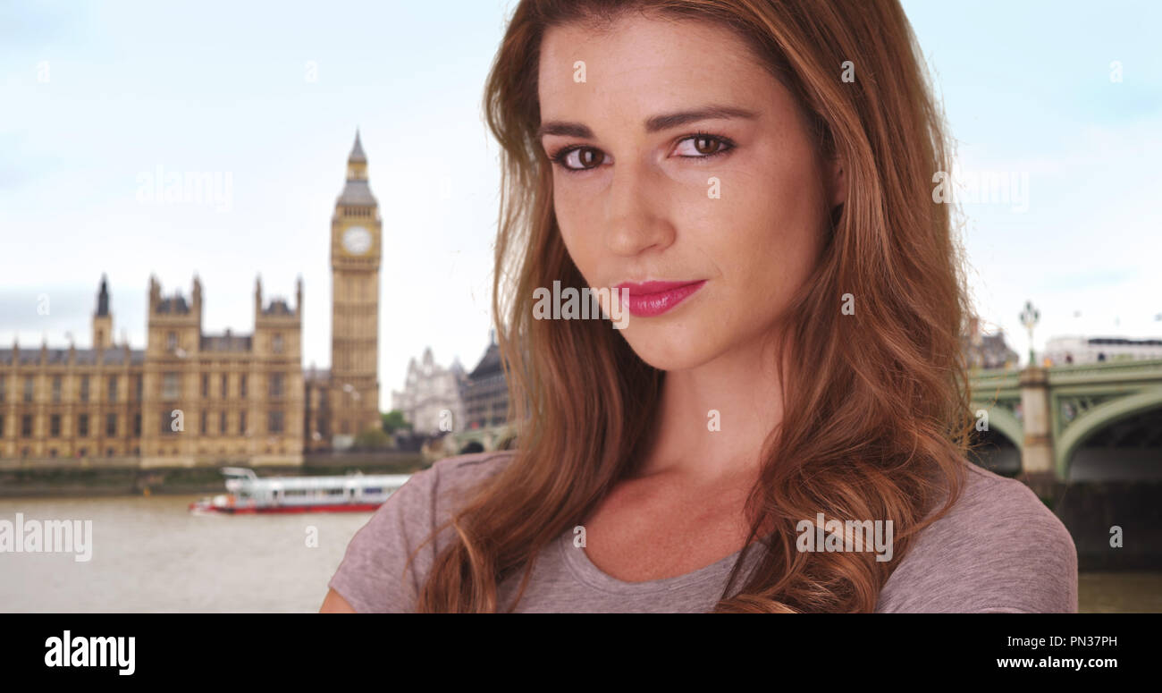 Pretty brown-haired white female smiling at camera in London near Big Ben - Stock Image