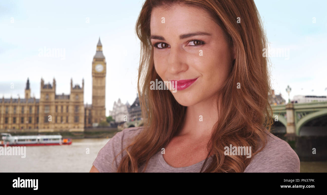 Pretty brown-haired white female smiling at camera in London near Big Ben Stock Photo