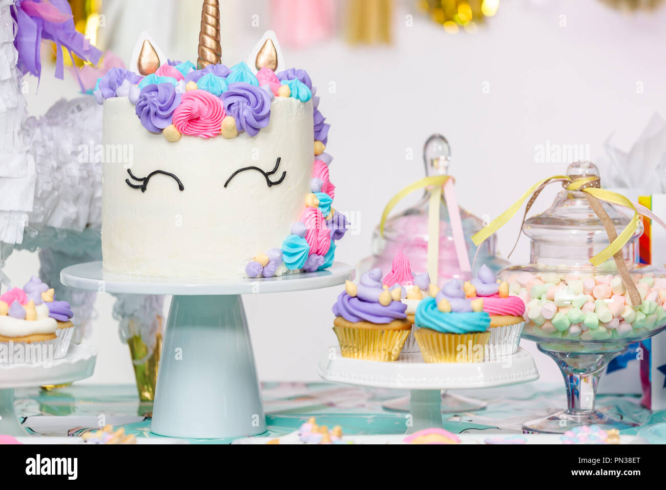 Little Girl Birthday Party Table With Unicorn Cake Cupcakes And Sugaer Cookies