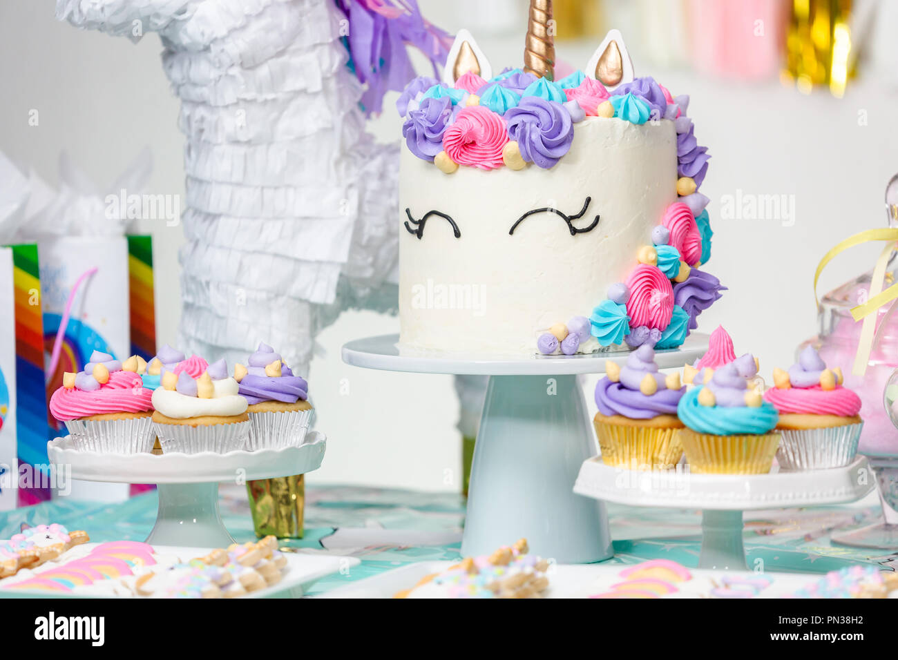 Little Girl Birthday Party Table With Unicorn Cake Cupcakes And