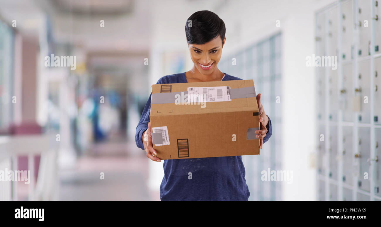 Black female shaking package excitedly in post office guessing what's inside - Stock Image