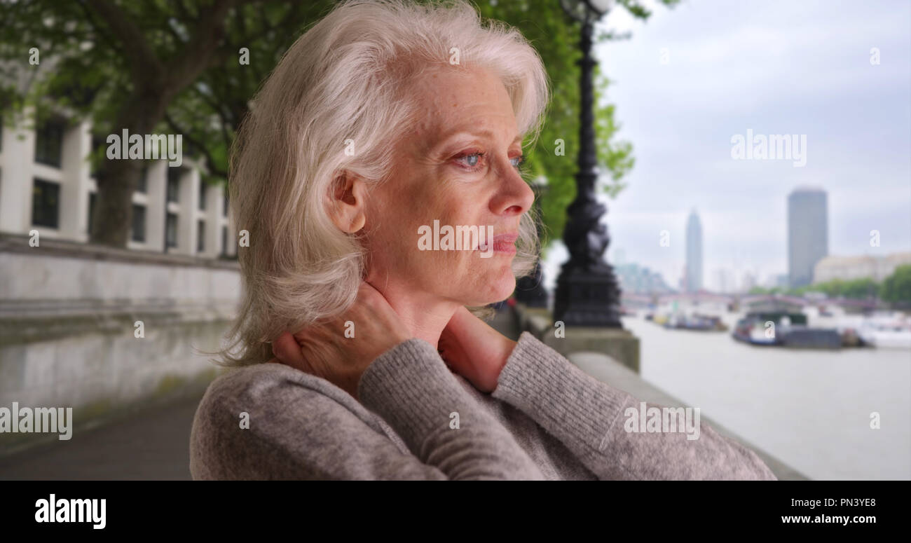 Tired woman tourist rubbing neck pain after long flight to London vacation - Stock Image