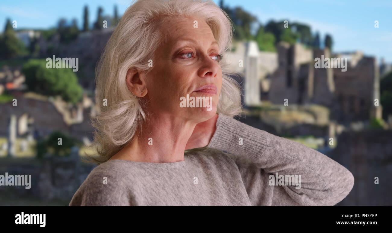 Exhausted woman tourist rubbing neck pain after long flight to Italian vacation - Stock Image