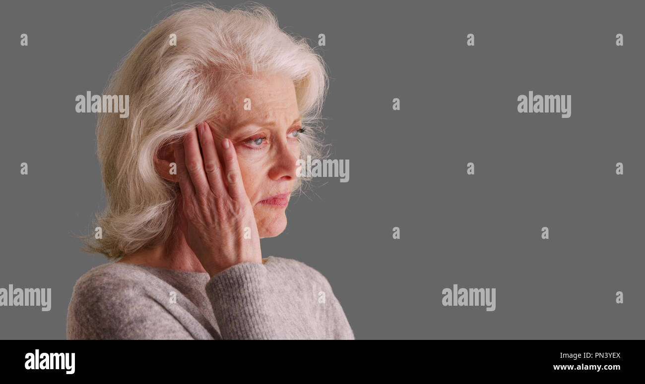 Close-up of sad looking elder woman on gray background touching her temples - Stock Image