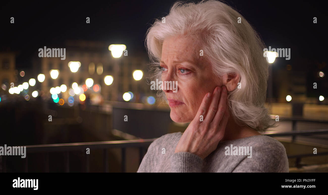 Close up of sad senior woman with headache in city at night - Stock Image