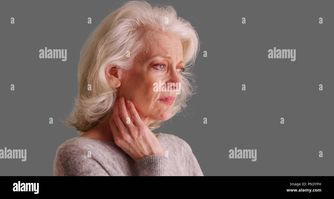 Mournful Caucasian female in her 50s looking concerned on gray backdrop - Stock Image