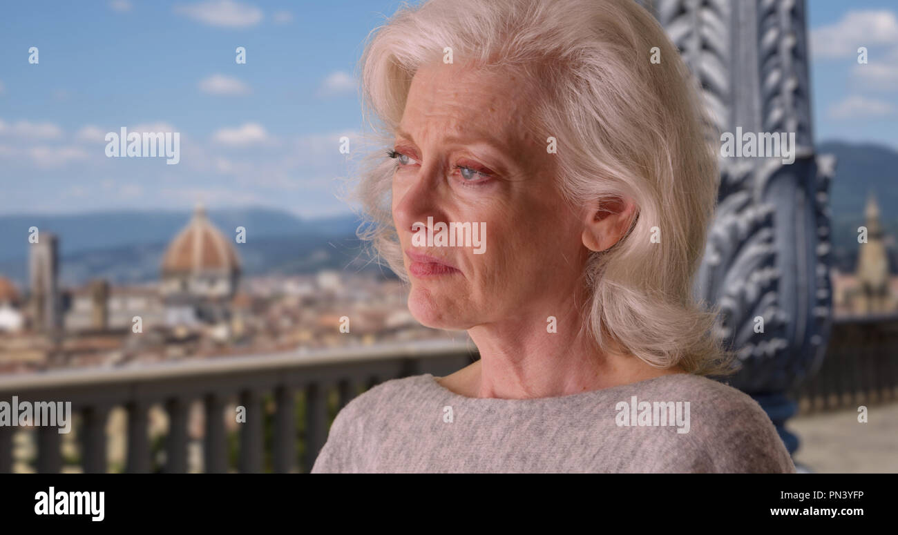 Sad depressed older woman looking at florence skyline in the day - Stock Image
