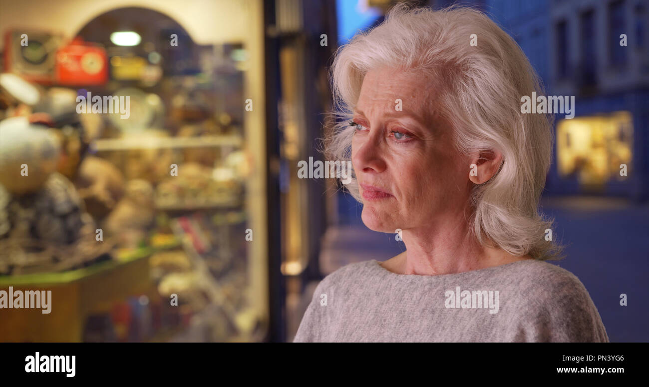 Stressed senior woman looking in store window shopping for gift at night - Stock Image